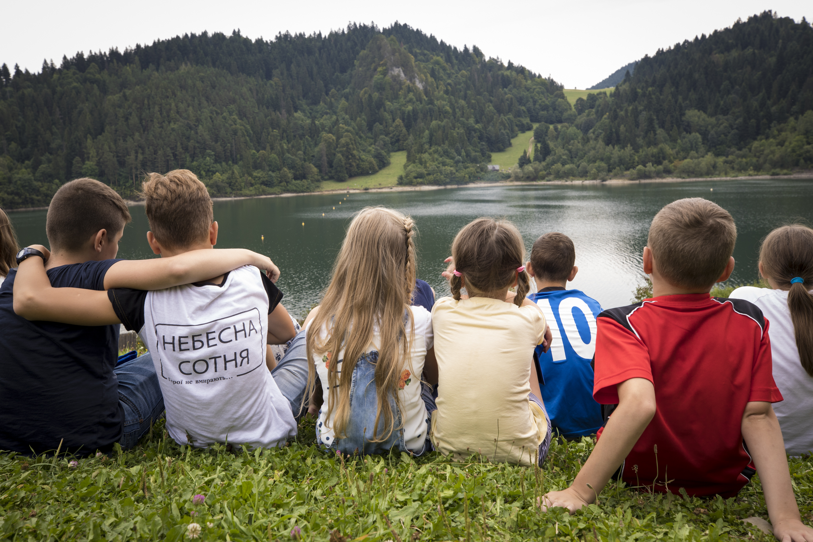 Children sit by a lake in Poland. All the children have lost parents or had parents severely injured in the conflict in Ukraine.